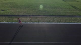 aerial shot of girl running at a track