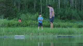 Camera looks over lake at father and son skipping rocks, rock splashes near camera lense