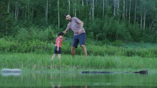 Camera looks through lake at father teaching young daughter to skip rocks, son enters frame and throws rocks