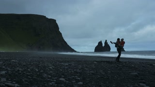 couple holding hands walking down black sand beach in Iceland