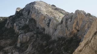 landscape of large mountain with girl rock climbing on wall