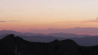 Landscape of Mountains at sunset, mountains are layered in pink and purples
