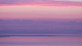 Landscape of Utah Lake with Mountains reflected at sunset, beautiful pink and purple colors