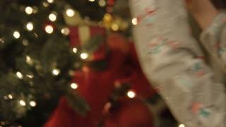 Little girl placing ornament on Christmas tree