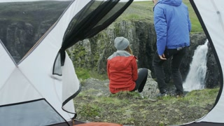 man gets out of tent, sits next to girl to check out view
