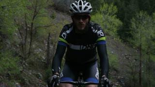 Man road biking through mountains
