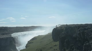man standing on edge of cliff taking photos of Dettifoss waterfall in Iceland