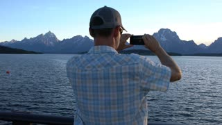 man taking photo of mountains with is cell phone