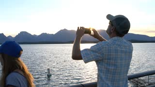 man taking photo of mountains with is cell phone in the Tetons