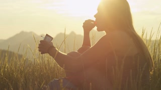 profile of woman sitting in field enjoying the mountains while enjoying snack