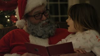 Santa reading Christmas book to children