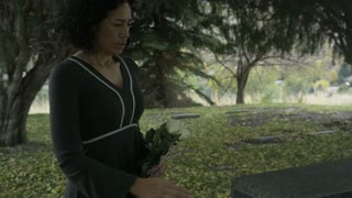Slow motion woman placing rose on top of grave stone in Cemetary