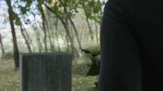 Slow motion woman placing rose on top of grave stone in Cemetery