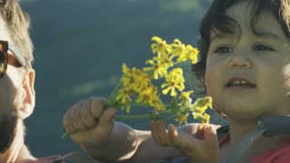 Small girls excited face as she holds yellow wildflowers in her hands
