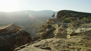 wide shot of woman doing yoga in the desert