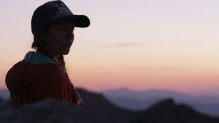 Woman hiker takes in view of Utah mountains at sunset, mountains are in pink and purple layers