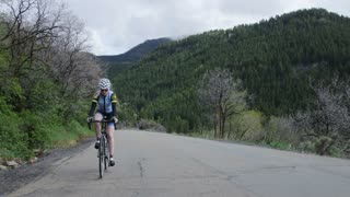 Woman road biking through mountains
