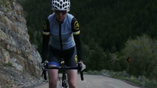 Woman road biking through mountains
