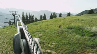 woman running down mountain trail under ski lift