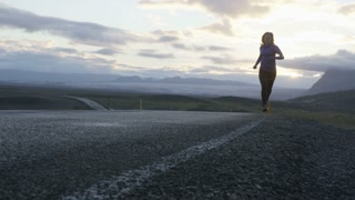 woman running on road in iceland