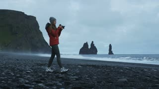 woman taking photos of black sand beach in Iceland
