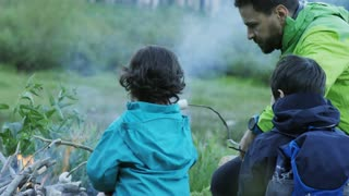 Young boy and girl roasting marshmallows while camping with their father