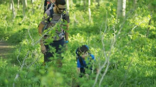 Young boy plays on trail while his father walks behind him while carrying his little sister