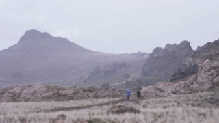 wide shot of two men running on trail while snow begins to fall