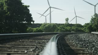 windmills blowing in background of railroad tracks