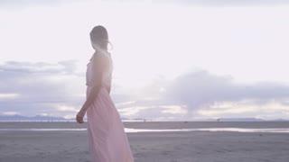 Woman in dress walks down beach