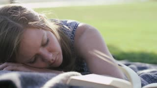 woman in park sleeping next to open book