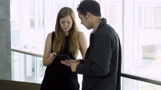 woman reviewing on ipad with man while at work in cool modern building
