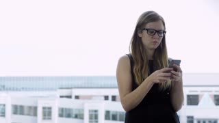 woman with glasses makes phone call