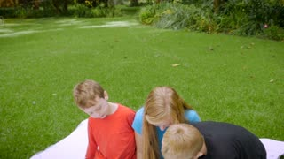 3 young cute kids or siblings, two blond haired and one red head boy play on a tablet outside - slowmo crane shoot
