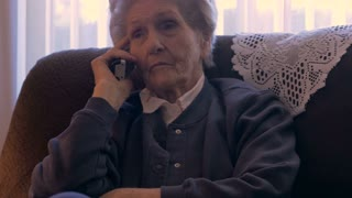 A 90 year old elderly woman in her home listens on a phone as she looks serious in 4k dolly
