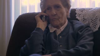 A 90 year old woman listening and talking on a land line, cordless, phone at her home while rubbing her eye in 4k dolly shot