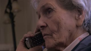 A 90 year old woman listens carefully to a phone conversation on a cordless telephone close up. She appears serious and maybe talking to a doctor, pharmacist, or other health care professional.