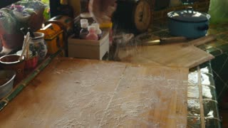 A baby boomer man in his 60s sprinkles flour to a wooden cutting board in preparation to roll out hand made pizza dough in his home kitchen