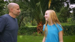 A bald father and blond haired daughter hug outside in a park - slowmo steadicam