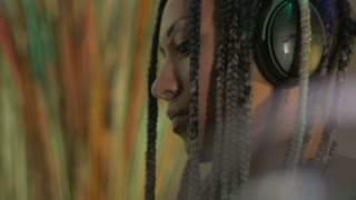 A beautiful millennial woman with long braids listening to music on headphones - room for text