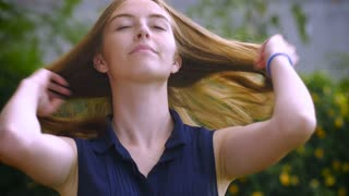A beautiful teen age girl with long blond hair smiles and plays with her hair in the wind in slow motion