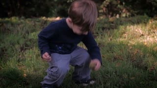 A beautiful young blond boy bending over and picking something up from the grass and then smiling and walking towards the camera in slow motion.