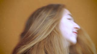 A beautiful young teenage girl twirls her lovely long brunette hair and smiles in slow mo