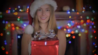 A beautiful young woman opens a Christmas present wearing a Santa hat in front of a fireplace decorated with colored lights.