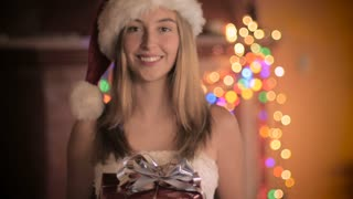 A beautiful young woman wearing a Santa hat gives a red wrapped wrapped gift with a silver bow and says Merry Christmas with colored lights flashing in the background