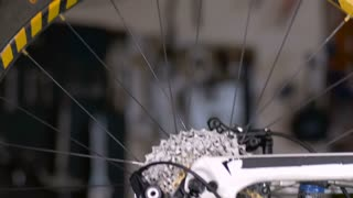A bike mechanic fine tunes the gears of a mountain bike with a screwdriver in his workshop