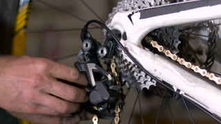 A bike mechanic threads a bicycle chain through a derailleur with his greasy, dirty hands