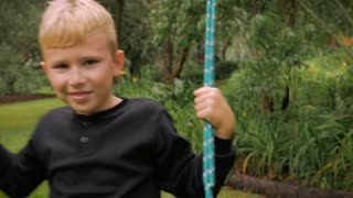 A blond boy having fun swinging on an old fashion swing - slowmo