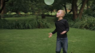 A blond haired young boy stops playing with a balloon to look at the camera - slowmo