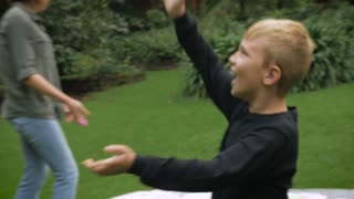 A blond young boy having fun outside with a balloon and his family - slowmo